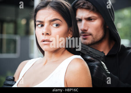 Man robber in hoodie threatening with gun to terrified young woman outdoors - Stock Photo