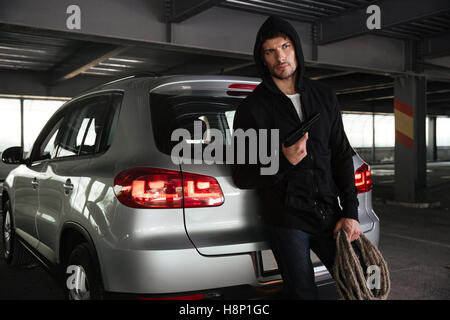 Criminal young man holding gun and rope near the car on parking - Stock Photo