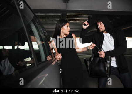 Angry man thief in hoodie stealing woman bag and treatening to her with gun on car parking - Stock Photo