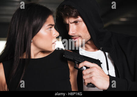 Closeup of scared young woman threatened with gun by criminal man in hoodie - Stock Photo