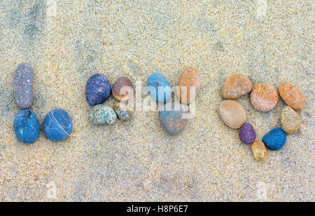 the word 'love' spelled out in stones lying on the sand. - Stock Photo