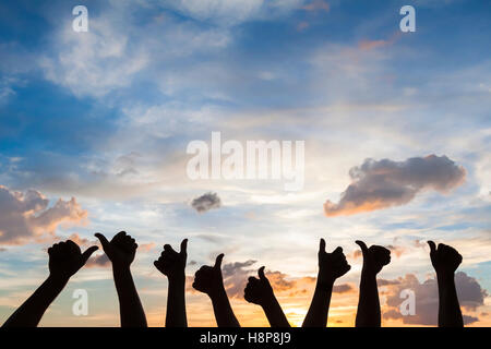 Silhouette of many people with thumbs up, symbol of like, satisfaction and agreement, sky background - Stock Photo