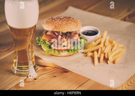 Fish and Chips Burger with fried potato straw, fresh salad  cold beer - Stock Photo