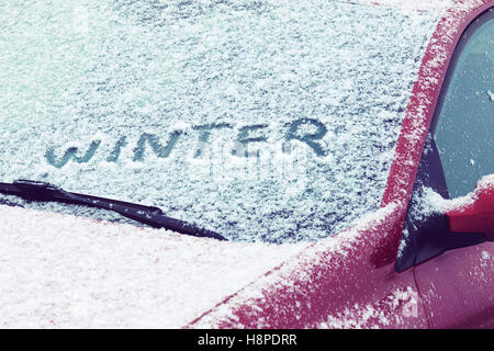 Word Winter written on a car windshield covered with fresh snow - Stock Photo