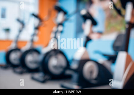 Aerobics spinning exercise bikes gym room with many in a row - Stock Photo