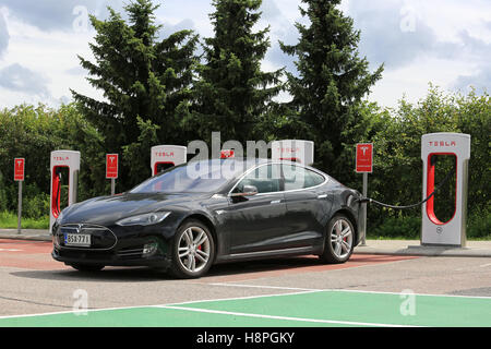 PAIMIO, FINLAND - JULY 17, 2016: Black Tesla Model S Electric car charging at Tesla Supercharger station in Paimio, - Stock Photo