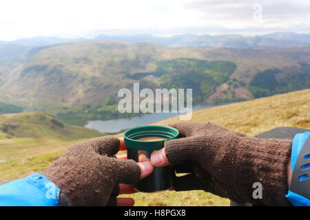 Model relaxing with a warm drink, enjoying the view from Helvellyn summit. Looking over Thirlmere lake and the mountains - Stock Photo
