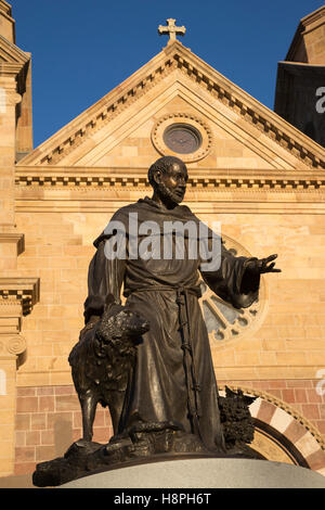 Bronze statue of St Francis with a wolf in front of the Cathedral Basilica of Saint Francis of Assisi - Stock Photo
