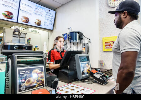 Vero Beach Florida McDonald's restaurant fast food interior counter cashier woman employee Black man ordering customer - Stock Photo