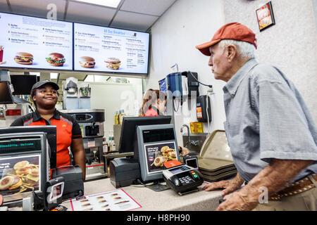 Vero Beach Florida McDonald's restaurant fast food interior counter cashier Black teen girl employee senior man - Stock Photo