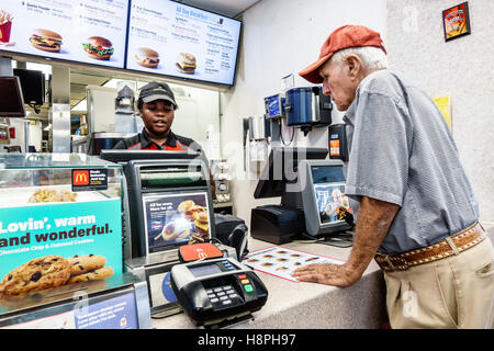 Vero Beach Florida McDonald's restaurant fast food interior counter cashier Black teen girl employee senior man - Stock Photo
