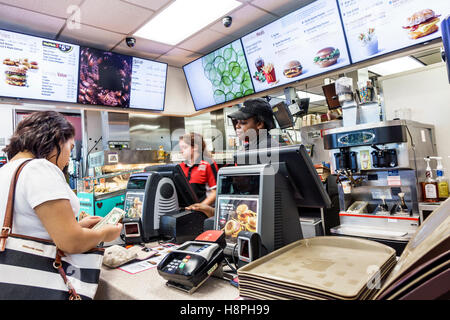 Vero Beach Florida McDonald's restaurant fast food interior counter cashier Black woman employee paying counting - Stock Photo