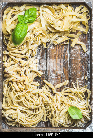 Various homemade uncooked Italian pasta in wooden tray - Stock Photo