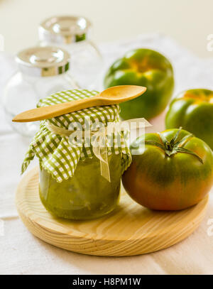 Green tomato chutney in a jar on a wooden surface - Stock Photo