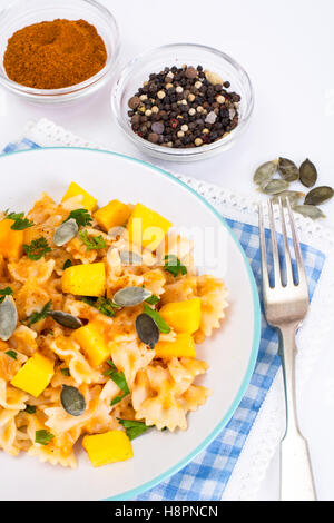 Farfalle with slices of pumpkin and parsley - Stock Photo