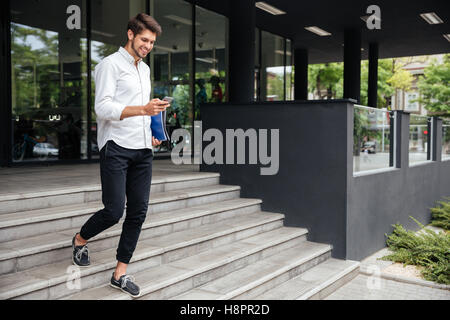Smiling attractive young businessman walking and using mobile phone near business center - Stock Photo