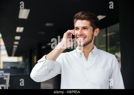 Portrait of happy handsome young businessman talking on mobile phone near business center - Stock Photo