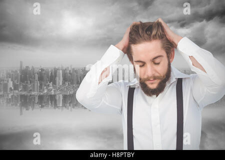 Composite image of frustrated hipster with head in hands - Stock Photo