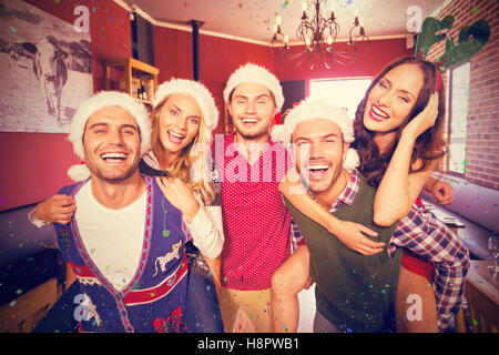 Composite image of portrait of men wearing christmas wearing giving women piggyback rides - Stock Photo