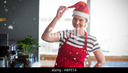 Composite image of portrait of waitress in santa hat standing with hand on hip - Stock Photo