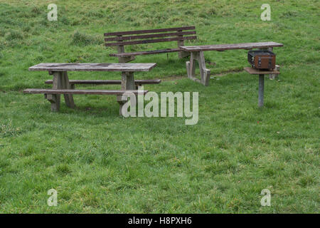 Picnic table, benches / bench seats. and fixed barbecue in public park area. - Stock Photo