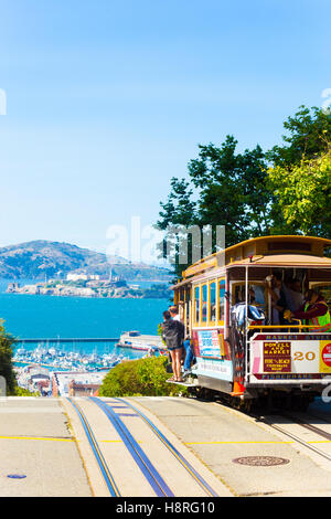An iconic cable car full of passengers at the crest of Hyde Street going over the edge toward the view of Alcatraz - Stock Photo
