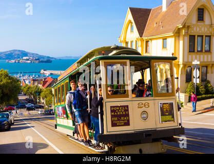 Closeup of approaching Hyde Street cable car full of people standing on outside platform enjoying steep hill ride - Stock Photo