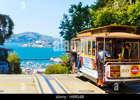 A cable car full of tourists at the peak of Hyde Street going over the edge toward the view of Alcatraz Island in - Stock Photo