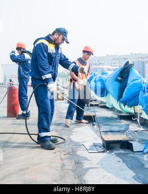 Workers waterproofing of seams on bridge