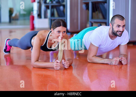 Photo of a woman doing pushups in a gym withe her personal trainer - Stock Photo