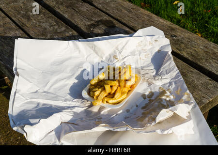 Portion of British chips or fries, in carton with wrapping paper on a sunny day. - Stock Photo