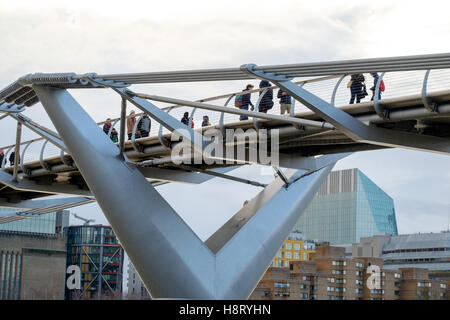 People crossing The Millennium Bridge over the Thames, London,United Kingdom. - Stock Photo