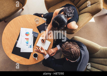 View from above of two business people planning work around table. Businessman and woman going through the to do - Stock Photo