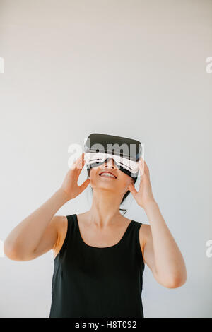 Vertical shot of young woman using the virtual reality headset against grey background. Happy female model wearing - Stock Photo