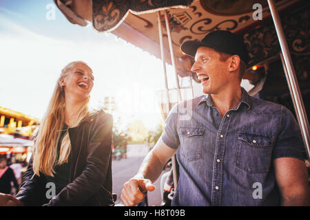 Laughing young friends riding on carousel in amusement park. Smiling couple on carousel ride. - Stock Photo