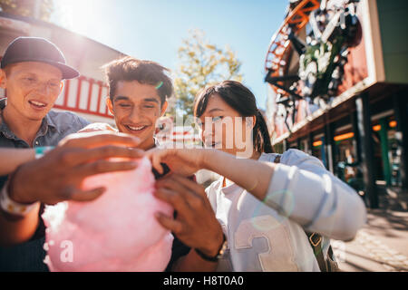 Young men and woman sharing cotton candy floss at fairground. Group of friends eating cotton candy in amusement - Stock Photo