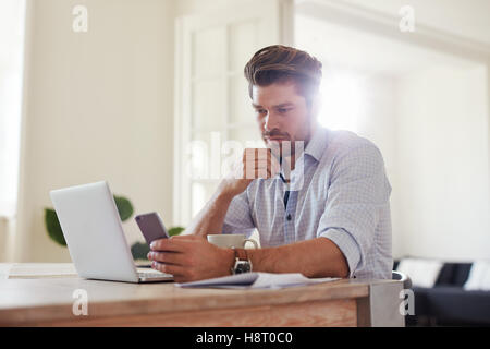 Indoor shot of young man reading text message on mobile phone while sitting at table at home. Business man at home - Stock Photo