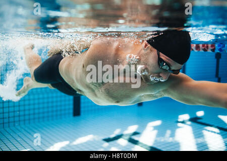 Professional male swimmer swimming in pool. Underwater shot of young sportsman practising for competition in pool. - Stock Photo