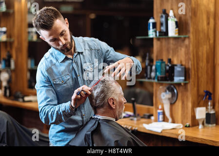 Old man having haircut by young specialist - Stock Photo