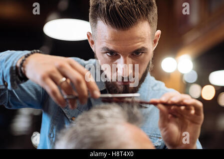 Close up of young male hairdresser cutting hair - Stock Photo