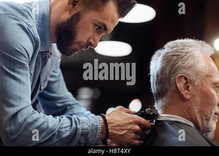 Hairdresser trimming neck of senior client - Stock Photo