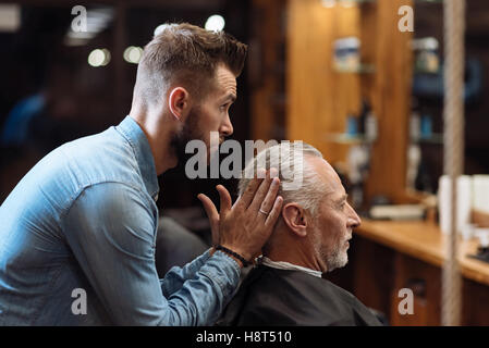 Handsome barber styling hair of senior man - Stock Photo