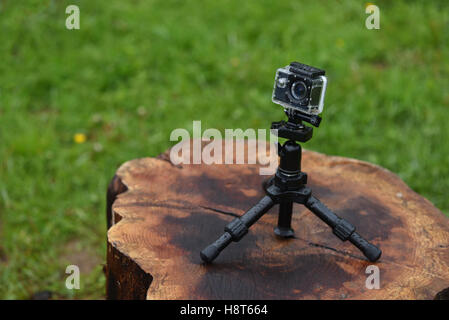 Action camera in rain with waterdrops on it, on a wet log, against green nature background - Stock Photo