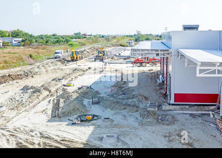 Landscape transform into urban area with machinery, people are working. View on construction site. - Stock Photo