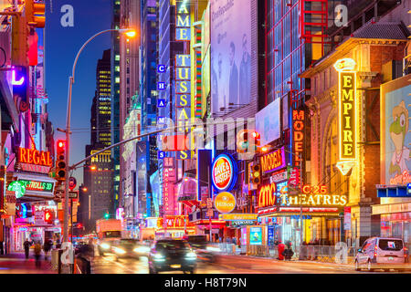 Traffic moves below the illuminated signs of 42nd Street in New York City. - Stock Photo