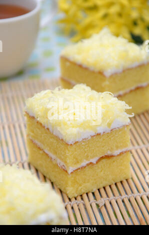 cake two layer with cheese as a toping, with a cup of hot tea as a background - Stock Photo