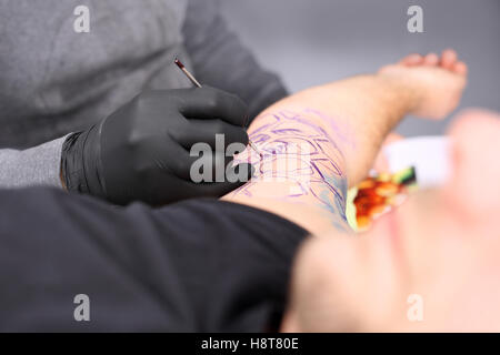 Tatoo drawing on his shoulder. Tattoo, tattoo artist does the tattoo on the man's hand. - Stock Photo