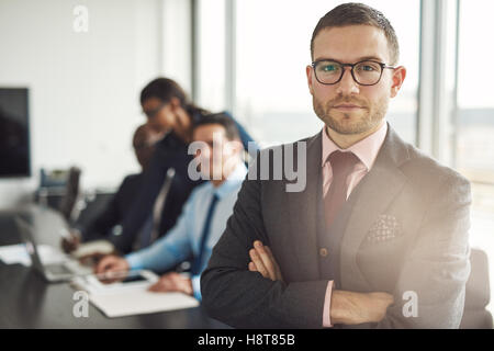 Handsome bearded professional in eyeglasses and tie standing with folded arms beside three busy coworkers in front - Stock Photo