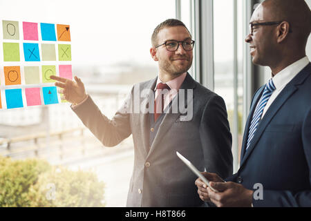 Two businessmen standing in front of a bright window with flare smiling as try to solve a problem laid out on colorful - Stock Photo
