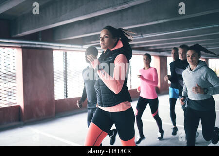 Attractive young urban runner pacing her team mates as she sprints through an undercover car park in a health and - Stock Photo